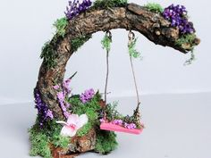 Every Fairy Garden should have it's own Fairy Swing.  .   Simple to do, all you need is a bent over piece of woody branch, some twine and a couple of screws to secure the twine to the leaning branch in your mini-fairy garden.   Now decorate to your heart's content with greenery and tiny flowers, and don't forget to mount everything on a platform covered in peat moss.