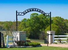 big stone columns supporting an arched name plate of ranch with simple garden on either side