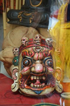 Skulls surround colorful Tibetan mask with large ears