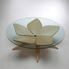 'Hana Table' by Shige Hasegawa  - inspired by origami, built of five flower-shaped plywood pieces forming a collective stand on a glass table without using additional screws or bolts.