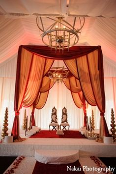 The ceremony featured a floor to ceiling mandap with traditional red and gold decor.