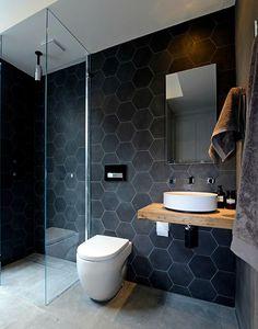 Questo piccolo bagno moderno utilizza grandi piastrelle in grès effetto pietra sul pavimento e piastrelle nere hexagonali effetto stone washed sulle pareti
