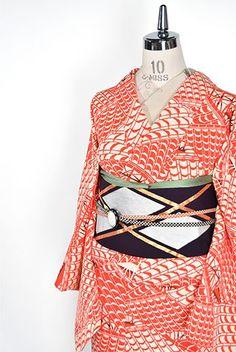 象牙色地に朱美しく染め出された甍の連なりが波のように美しい模様を描き出す洒脱な遊び心を楽しむ正絹縮緬の袷着物です。