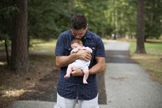A father and his newborn baby son  surrounded by gorgeous trees in a park