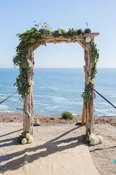 Beach wedding ceremony decor idea - wooden arch with lush white flowers + greenery {Town Country Studios}
