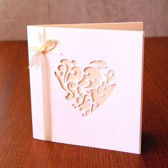 Svatební+oznámení+LILLY+s+výřezem+-+champagne+Svatební+oznámení+o+velikosti+12,5+x+12,5+cm.+Vrchní+bílý+papír+s+krásnou+texturou+a+výřezem+filigránového+srdce.+Vnitřní+papír+je+pouze+vložen+a+svázán+s+bílým+atlasovou+stužkou+stejné+barvy.+Vnitřní+papír+a+stužku+je+možné+změnit+na+barvu+dle+vašeho+přání.+Text+i+písmo+je+pouze+ilustrativní,+bude+upraveno+dle...