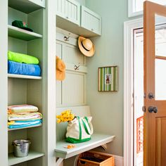 An awkward entry gains practical charm with a tower of open shelves, top cabinets with tilt-up doors, and a bench with curved supports. Simple battens hold coat hooks. Durable paneling and a soft shade of green paint knit the pieces together.