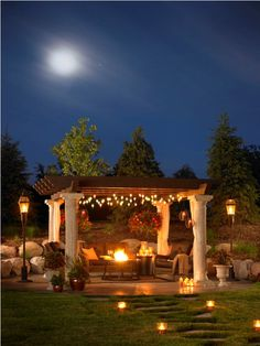 Tuscany Pergola nighttime view with contrast of columns to wood beam top. Beautiful stone landscaped berm behind the patio and walking stone steps.  |  http://homesweethome-sibirochka.blogspot.com/2011/04/wow-factor.html