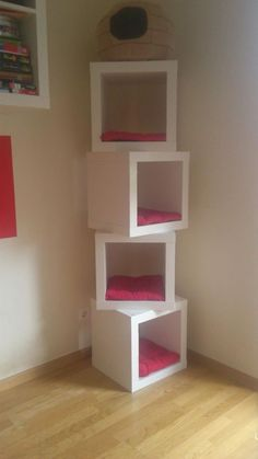 cat tower made with Ikea cubes and chair cushions .