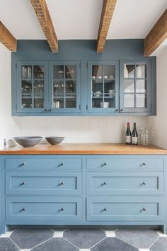 New kitchen with light blue cabinets, butcher block countertops, exposed beams and glass front cabinets.
