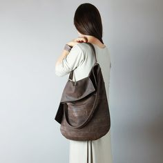 TUULI is a slouchy hobo with horizontal, geometric patchwork at the bottom.  Its made of buttery soft and beautiful, highest quality italian nubuck leather in chocolate brown color. Very natural shade. Matt finish. It is big, simple and asymmetric.  Bag is made of 100% natural leather. Lined with pure cotton in chocolate color.  Two pockets inside. It fits A4/Letter paper format. Hardware in brass color.  Dimensions: W: 14,4 (36 cm) H: 16 (40 cm) Handmade with ♡ in our little studio.