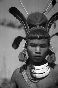 India | Young Konyak Naga man with wool ear tufts, boar's tusk necklace and hat with feathers and goat's hair. Wakching, Nagaland, Mon District. 1937. | ©SOAS, Nicholas Haimendorf