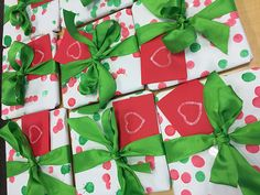 Personalized wrapping paper by our preschoolers. They used red and green dot painters to embellish plain, white paper.  We added a green bow and gift card with a white stamp.