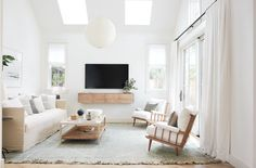 slipcovered sofa, midcentury chairs, skylights, small living room