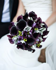 This elegant bouquet is made of eggplant calla lilies, fringed tulips, green hypericum berries, and dusty miller leaves.
