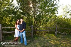 Country chic engagement portraits. Rustic fence, cowboy boots.