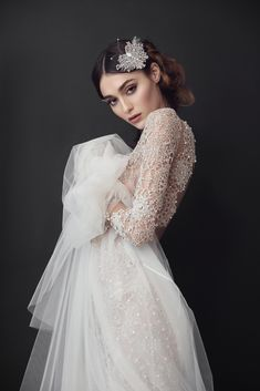 Silver French embroidery gown decorated with mounted crystals. Bodice with cut out sides and keyhole back. Soft tulle train.