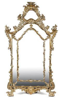 Exceptionnelle et spectaculaire glace à pare-closes  en bois argenté et sculpté à décor de coquilles, feuillages, guirlandes de fleurs et motifs feuillagés.  Travail italien du XVIIIe siècle.