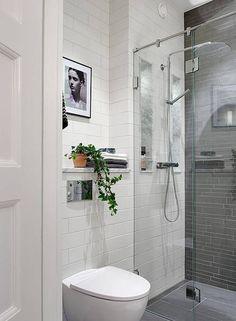 Ściany wyłożone płytkami w tej łazience prezentują się niezwykle efektownie. To dlatego, że tradycyjną cegiełkę z płytek subway zestawiono z szarą nieregularną mozaiką przy natrysku. Białe kafle tworzą subtelną fakturę, na której tle fotografia w czarnej ramie nabrała wyrazistości.