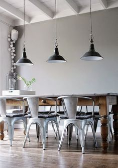 low hanging statement lights, centred tabled with curved back tuck in chairs. Grey walls Wooden floor