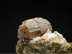 Axinite-(Fe), Ca4Fe2+2Al4[B2Si8O30](OH)2, Albite,  East slope, Le Catogne, Sembrancher, Bagnes Valley, Wallis, Switzerland.  Copyright © Christian Bracke