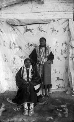 """She Came Spotted :: Western History ~ Portrait of She Came Spotted and an unidentified Native American Sioux woman, posed outside on a fur skin rug in front of a painted backdrop of a Lakota style Indian war record, Pine Ridge Agency, South Dakota. Photo: ca. 1890. - One problem with this photograph is we're not told which one of the women is """"She Came Spotted"""", at a guess I'll go for the lady seated. At least that's a 50% chance of being right! Love the painted backdrop. Wonderful."""