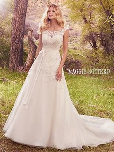Maggie Sottero Ophelia.                      Embroidered lace appliqu�s cascade over the bodice, illusion sweetheart neckline, and illusion cap-sleeves of this gorgeous A-line, featuring a keyhole back and tulle skirt. Finished with covered buttons over zipper closure. Style includes grosgrain ribbon belt.