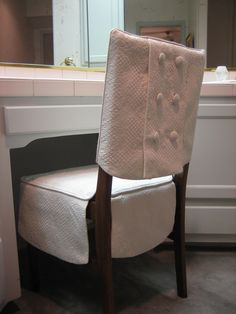 This is my Double Buttoned Chair Suit®, made of cream colored matellasse and both jacket and skirt are lined.  The jacket has a center back panel below the covered button trim.  The skirt has ivory satin ties to attach to chair (not shown) and flat, curved lower edges.  Each set is custom made to fit your chair.  Dry clean only.