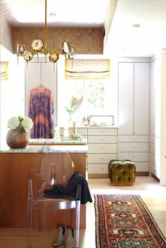 A spacious walk in close with white storage and drawers, a patterned runner rug, and a luxe chandelier