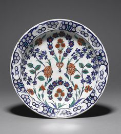 Dish. Symmetrical lobing outside and at rim, two flower compositions on vertical axis with scrolls of hyacinths, roses, cornflowers. Made of black, cobalt, green, red (bole) painted and glazed and bevelled ceramic, pottery.