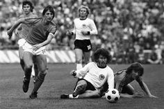 Dutch forward Johan Cruyff (left) runs past German defender Paul Breitner, sitting on the pitch during the final of the Soccer World Cup at the Olympic Stadium in Munich, Germany, July 7, 1974. (AP)