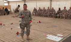 Photos shows a army colonel givng an opening statement at the start of a sand table briefing