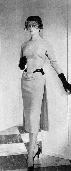 1954 Model in elegant dress with draped panel accent by Howard Greer, Harper's Bazaar,