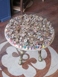 Collection of Wooden Thread Spools - so clever - simply arranged on a round side table, nicely topped with a glass round table topper. So unique for a guest room <3