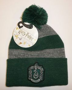 35dd9f7e19f This is a very nice knit striped beanie hat. The cuff features a Slytherin  patch on the front. Top has a little pom   poof on it. Made by Bioworld.