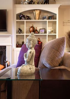 Designer Kimberly Lyons chose just the right trinkets to display on the matching bookcases, which were installed on either side of the fireplace wall to give the family room a dash of elegance. The green-hued Buddha, placed adjacent to the couch, also creates an unexpected but lovely decorative addition.