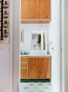 Banheiro com marcenaria com detalhes de formica dourada e hidráulico verde.