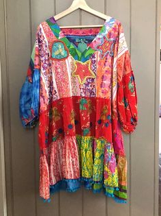 Bright oversized patchwork cotton dress in mixed floral and prints. Accented by beaded embroidery and pompom trim. One size tunic style. across bust under arms and length. Beaded Embroidery, Cotton Dresses, Elsa, Kimono Top, Arms, Tunic, Bright, Floral, Sleeves