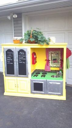 Old horizontal entertainment center transformed into a child's kitchen play area.