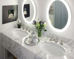 mitered countertop drop edge lit circular mirrors and polished nickel give this bathroom a glamorous