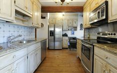 A delightful eat-in kitchen features light wood cabinets, a Delft tiled backsplash, state of the art stainless appliances, granite countertops and an efficient workstation with a desk.
