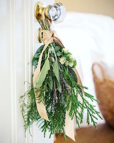 """We love the idea of perfuming the home with natural adornments such as this sweetly scented herb bouquet accented with lavender and tied beautifully with ribbon on a bedroom door. In """"Scents of Graciousness"""" in our new January/February issue, we share many more ideas for filling your home with fragrance."""