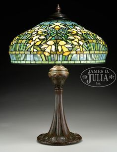 """TIFFANY STUDIOS DAFFODIL TABLE LAMP. Tiffany Studios table lamp has leaded glass shade with yellow, cream and amber daffodils along with shaded green leaves and stems against a mottled light blue slightly opalescent background. Shade is signed on interior rim """"Tiffany Studios New York 1919"""". Shade rests on a Tiffany Studios onion base with onion decoration surrounding the foot and top of the base which is complete with a three socket cluster and acid etched heat cap. Finished in a r..."""
