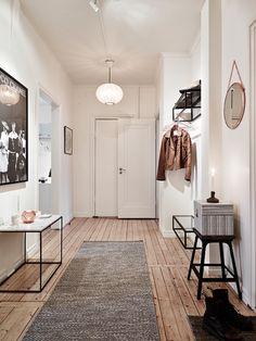 Aranżacja przedpokoju,jak urządzić przedpokój,drewniana podłoga w korytarzu,czy drewniana podłoga pasuje w przedpokoju,białe ściany w korytarzu,długi przedpokój,jak urządzić długi pkorytarz,wiesaki w przedpokoju,meble do przedpokoju,graf