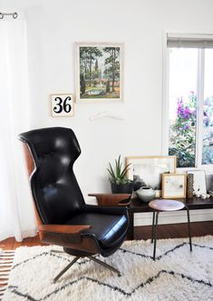 Black leather eames-like lounge chair, three-legged stool and long, low bench all from mid century modern finds; '36′ painting by lisa congdon; vintage paint by numbers via hazel & gerties.