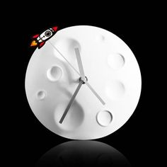 Watch time fly and jet around the moon in 60 seconds. A solid metal dome-shaped wall clock, with an orbiting rocket, circling in time and space. Watch as the seconds fly by. The battery operated wall clock is a great astronomical addition to any room. Wall Clocks Uk, Moon Clock, Playroom Storage, Wall Clock Design, Battery Operated, Designing Women, Home Accessories, Branding Design, Bebe