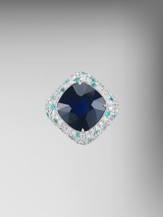 From the Bespoke Collection by Paolo Costagli The AGL Certified Unheated Blue Sapphire and Paraiba Type Tourmaline Bon Bon Ring is handcrafted with a Cushion-shaped blue sapphire weighing 12.27 carats set in 18kt white gold, further enhanced with pave-set round brilliant diamonds weighing 2.86 carats and pave-set Paraiba-type tourmaline weighing 0.82 carats.