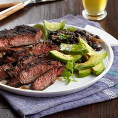 Carne Asada with Black Beans | Rick Bayless serves this classic dish that combines grilled marinated steak, fried plantains, homemade black beans and fresh guacamole. To make it easier, trim the dish back to a simple duo of spice-marinated rib eye steaks and canned black beans served with avocado.