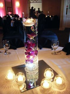 Cylindrical centerpiece - Purple dendrobium orchid, floating candles, LED lights to illuminate the base of the arrangements