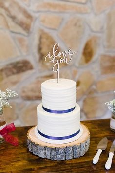 "Such a beautiful and simple white wedding cake with navy blue ribbons!  And love the gold ""i love you"" cake topper.  Perfect wedding cake for a rustic wedding. Taken at THE SPRINGS in Weatherford.  Book your free tour today! Photographer:  Anna Smith Photography #rusticwedding #rusticweddingcake #blueweddingcake #simpleweddingcake #marinewedding #militarywedding #airforcewedding"